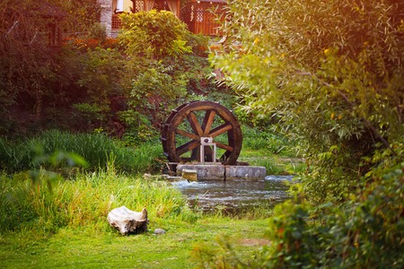 waterwheel: Old wooden waterwheel watermill on a horse farm. The old water wheel covered with moss. Flowing water to the mill. Old technology energy water movement