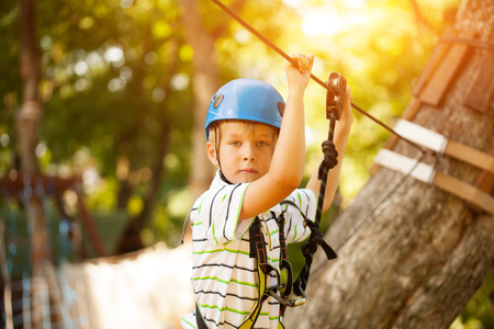 Happy boy at adventure and climbing ropeway activity in forest