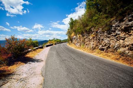 遠くの山の中の舗装道路