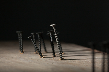 Screws on wooden surface - Business leadership, teamwork power and confidence concept