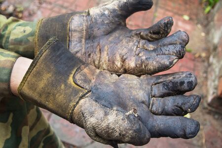 man's hands in burned leather gloves