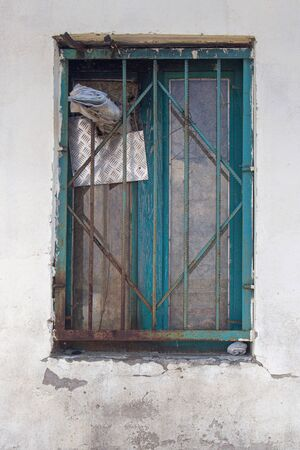 ugly blue wooden window closed with steel bars