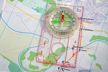 travel sport compass lies on a map to determine azimuth movement
