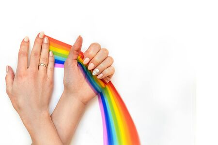 Painted rainbow in hand with unicorns manicure. White background with empty space.