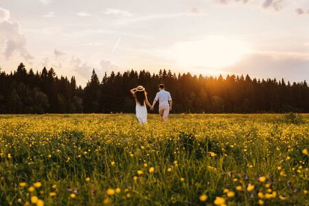 A couple in love runs across the field. Back view. Sunset light.