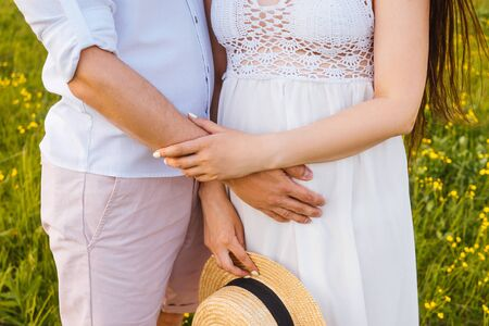 Pareja de embarazo en el campo con sombrero. Sin cabezas ni piernas, de cerca.