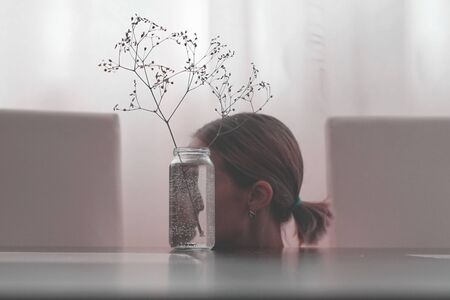 The girls face reflected in a glass jar. Look into yourself. The psychological concept. Stock fotó