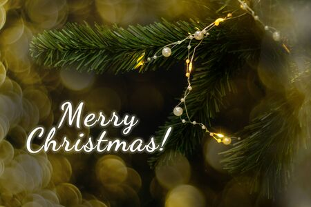 Fir branch on black background with garland. Lettering Merry Christmas and golden bokeh. Stockfoto