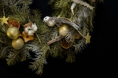 Part of Christmas wreath from cotton, snow cones, dry orange and apple slices, cinnamon sticks, gold christmas tree balls, bird and gold stars on a black background. Top view. Stockfoto