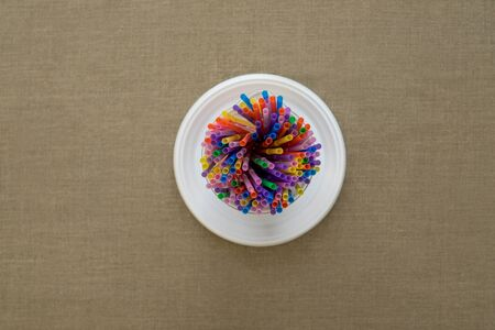 Top view on multi-colored disposable tubes in plastic plate on canvas. Environmental concept. Flat lay. 写真素材