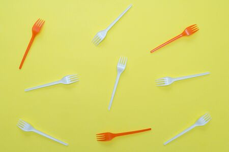 Plastic white and red forks on yellow background. Environmental concept. Flat lay.