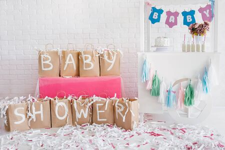 Decoration for baby shower with candy bar. White brick wall on background. Paper show.