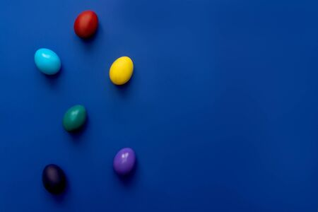 Color easter eggs over blue background. Easter hipster concept. Flat lay, copy space. 스톡 콘텐츠