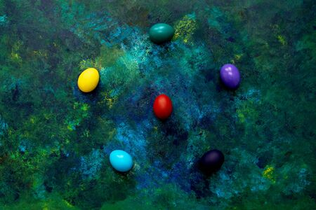 Color easter eggs on blue green oil paint mixed background. Easter hipster concept. Copy space.