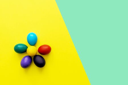 Color easter eggs as flower on yellow background. Easter hipster concept. Copy space on turquoise background. 스톡 콘텐츠
