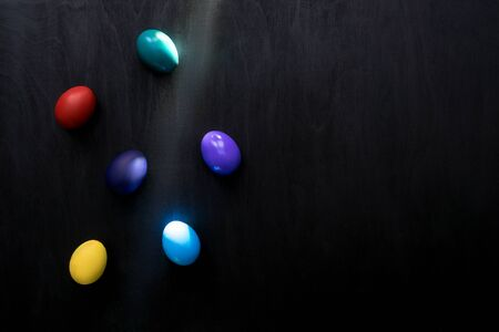 Color easter eggs in sunbeam over black wooden background. Easter hipster concept.