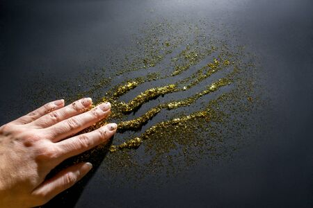 The hand leads along the sparkles and leaves a mark. Sparkles sparkles. Black background. 스톡 콘텐츠