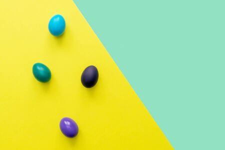 Color easter eggs over mint and yellow backgrounds. Easter hipster concept. Copy space. Zdjęcie Seryjne
