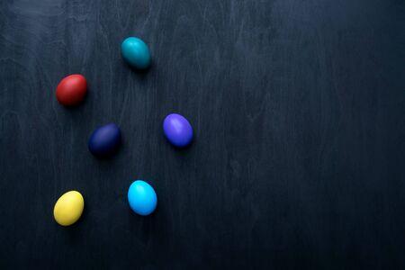 Color easter eggs over black wooden background. Easter hipster concept.
