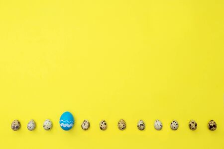 Row from quail and one easter eggs over yellow background. Place for text. Easter hipster concept. Eggs as symbol months. 스톡 콘텐츠