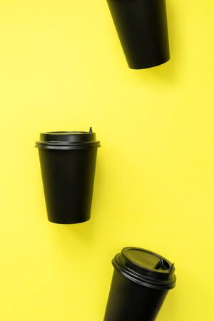 A pattern from a disposable coffee cup on a yellow background. Black craft glass for coffee or tea.