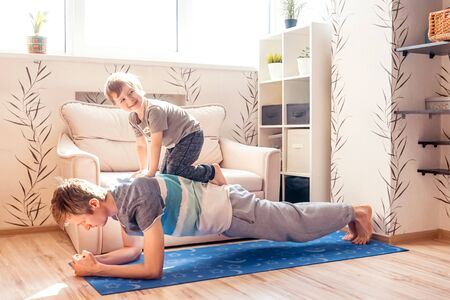 Father make plank with son at home. Fitness together in quarantine.
