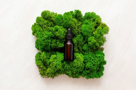 top view of bottle with natural oil in green moss on white wooden background. Archivio Fotografico