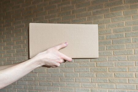 Delivery box closed in hands on brick wall backgraund. Foto de archivo