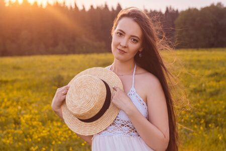 Young pregnant woman in the field in long white dress. Sunset light. Standard-Bild