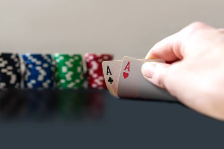 Person showing her deck two aces at the poker game. Chips on background.