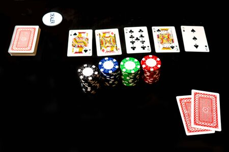 Two cards, stack and chips, poker game. Black background, copy space. Foto de archivo