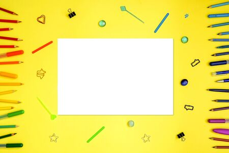 Stationery on yellow. Flat lay. Rows of tools as frame, gradient rainbow colors. Empty white blank with place for text.
