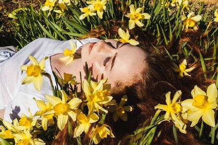 Portrait of young red-haired beautiful girl lying on narcissus. Front view. Concept of spring and summer youth happiness.