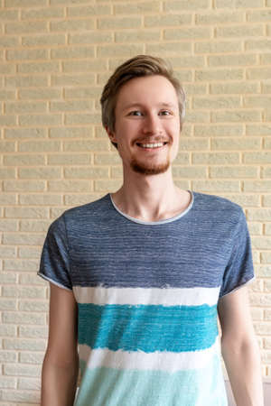 Smiling young man with red beard on brick wall background at home.