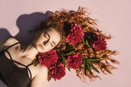 Close up portrait of young ginger curly girl with flowers peony in hair above. Top view, close eyes. Concept of spring and summer youth happiness.