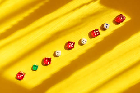 Dice diagonal on a yellow background, beautiful light and shadows. Playing a game with dice. Rolling the dice concept for business risk.