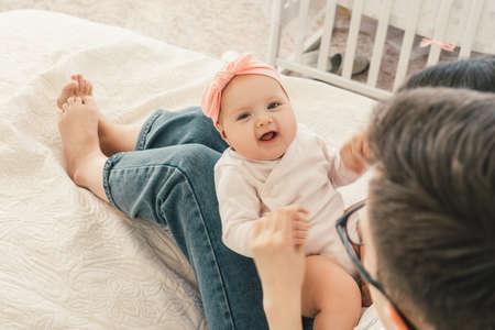 Cute baby girl lie on mothers legs. At home. Top view. 版權商用圖片