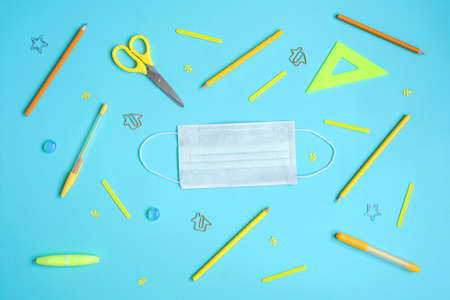 Stationery on blue. Bright stylish flat lay. Different yellow tools with white protective mask in center.