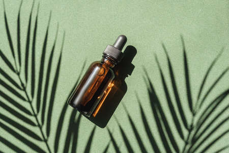 top view of Blank amber glass essential oil bottle with pipette on green background with tropical leaves shadows. Archivio Fotografico