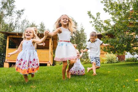 Happy kids running in garden on grass. Summer time. Foto de archivo
