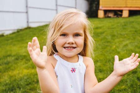 Happy childhood: Little girl having fun on grass. Close up portrait of little beautiful girl.