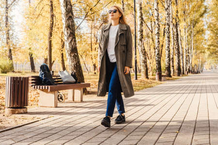 Business woman in coat walk in the autumn park, bottom view. Autumn park, sunny day.