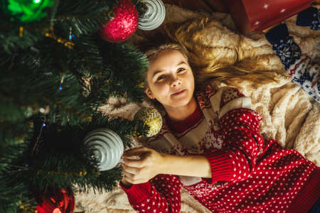 The woman in ugly christmas sweater lies under the Christmas tree and smile. New Year's concept. Decorated Christmas tree with baubles. Stock Photo
