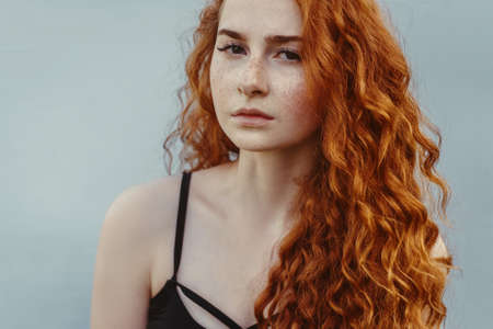 Close-up portrait of cute ginger woman with red curly hair on light blue background. Standard-Bild