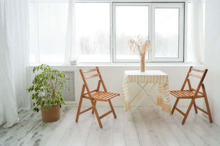 Table and two chair. Beautiful light and wooden interior. Cozy home, minimilaism. Table and two chair.