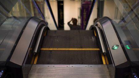 escalator in the mall, low light, green arrow