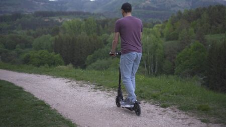 man riding an electric scooter in the park on nature