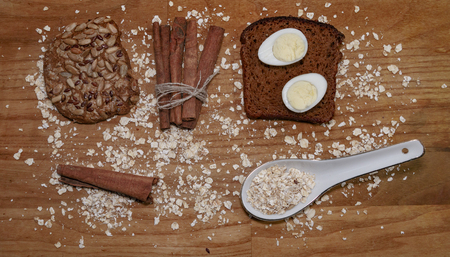 quail eggs on a black bread and oat chips and cookie and a cinnamon stick on a wooden table