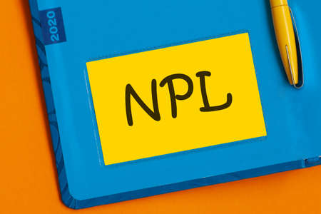 The word NPL is written in black marker on the yellow paper for notes. NPL - Non Performing Loan acronym, business concept background. Concept
