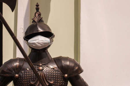 armor of a knight with a medical mask during quarantine at the entrance to a restaurant.